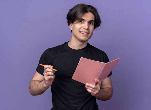 Lächelnder junger gutaussehender kerl mit schwarzem t-shirt mit notizbuch mit stift isoliert auf lila wand