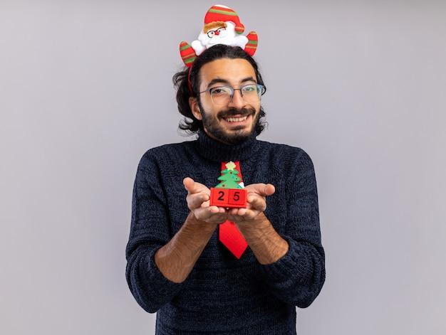 Lächelnder junger gutaussehender kerl mit weihnachtskrawatte mit haarreifen, der weihnachtsspielzeug isoliert auf weißer wand hält