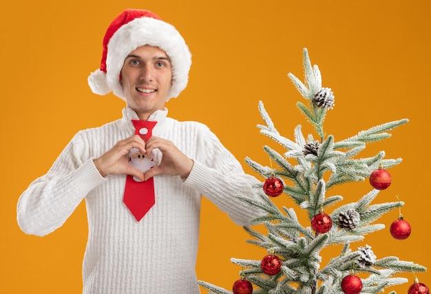 Lächelnder junger gutaussehender kerl mit weihnachtsmütze und weihnachtsmann-krawatte, der in der nähe des geschmückten weihnachtsbaums steht und ein herzzeichen tut, das isoliert auf der orangefarbenen wand aussieht?