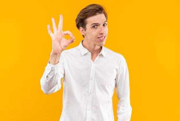 Lächelnder junger gutaussehender kerl mit weißem hemd, das drei isoliert auf orangefarbener wand zeigt