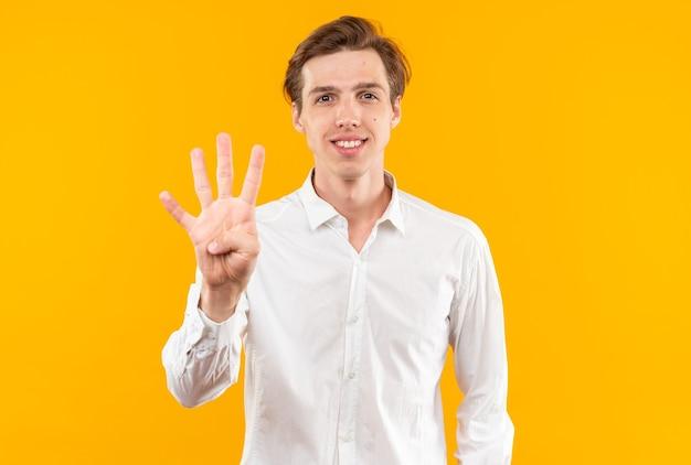 Lächelnder junger gutaussehender kerl mit weißem hemd, das vier isoliert auf oranger wand zeigt