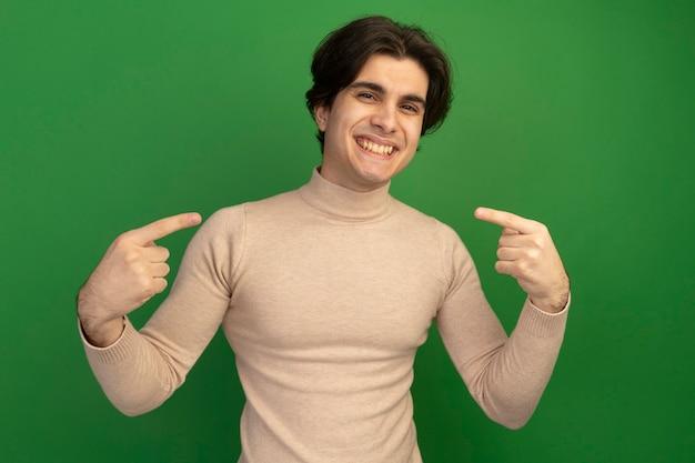 Lächelnder junger gutaussehender kerl zeigt auf sich selbst isoliert auf grüner wand