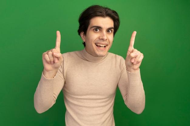 Lächelnder junger gutaussehender kerl zeigt nach oben isoliert auf grüner wand