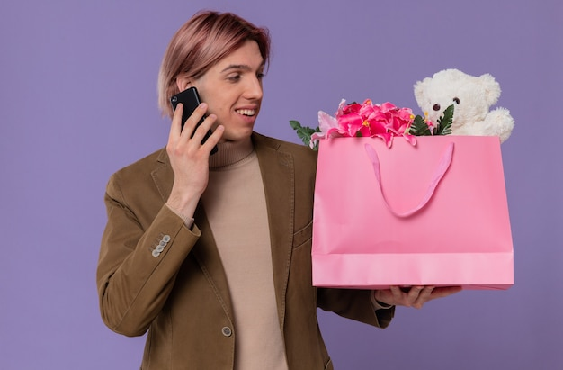 Lächelnder junger gutaussehender mann, der am telefon spricht und rosa geschenktüte mit blumen und teddybär betrachtet