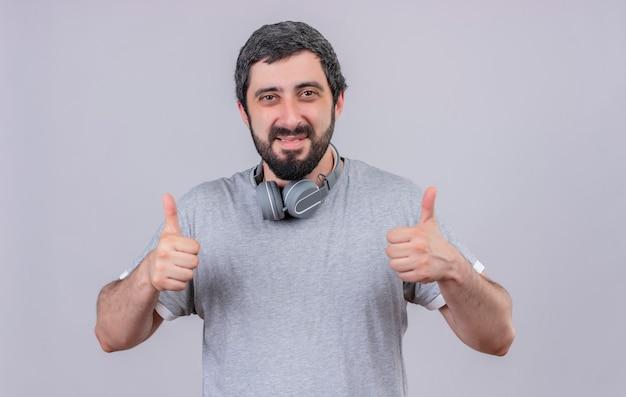 Lächelnder junger gutaussehender mann, der kopfhörer am hals trägt und daumen oben auf weißer wand isoliert zeigt