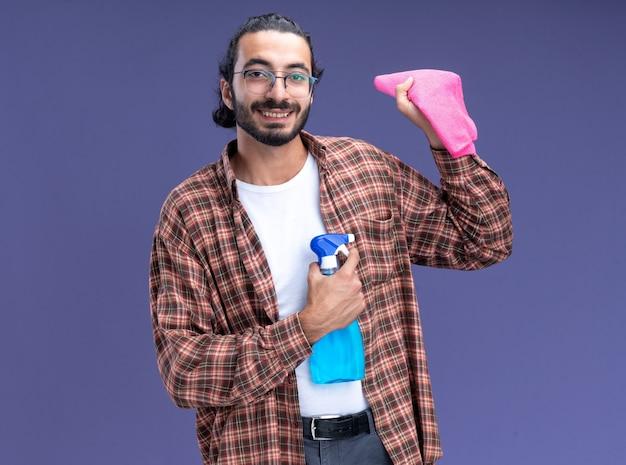 Lächelnder junger gutaussehender putzmann mit t-shirt mit sprühflasche mit lappen isoliert auf blauer wand