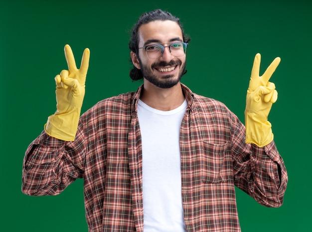 Lächelnder junger gutaussehender putzmann mit t-shirt und handschuhen, der eine friedensgeste isoliert auf grüner wand zeigt