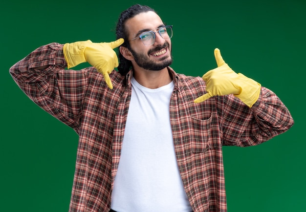 Lächelnder junger gutaussehender putzmann mit t-shirt und handschuhen, der telefonanrufgeste isoliert auf grüner wand zeigt