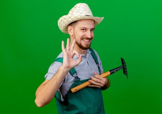 Lächelnder junger gutaussehender slawischer gärtner in uniform und hut, der rechen hält, der ok zeichen lokalisiert auf grüner wand tut