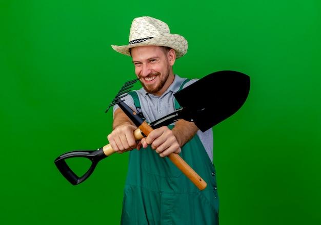 Lächelnder junger gutaussehender slawischer gärtner in uniform und hut, der rechen und spaten ausstreckend macht und keine geste mit ihnen macht