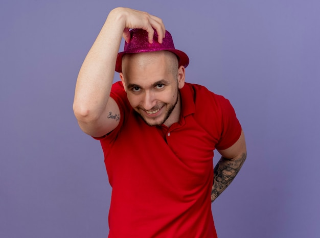 Lächelnder junger gutaussehender slawischer party-typ, der partyhut trägt, der es betrachtet kamera betrachtet, die hand hinter dem rücken lokalisiert auf lila hintergrund mit kopienraum hält