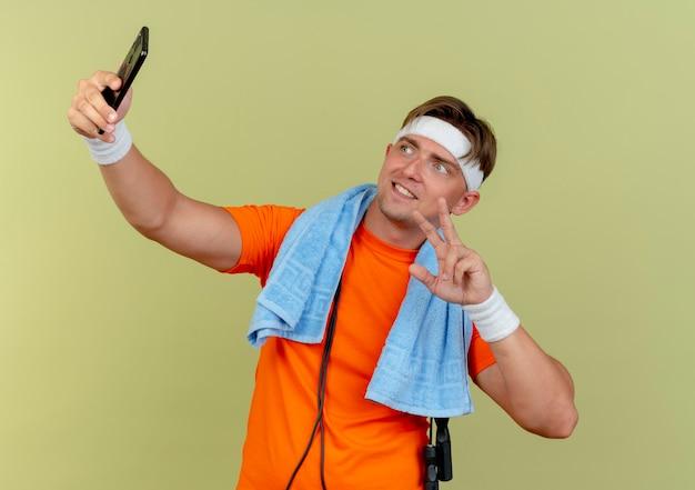 Lächelnder junger gutaussehender sportlicher mann, der stirnband und armbänder mit handtuch und springseil um den hals trägt und friedenszeichen tut, das selfie lokalisiert auf olivgrüner wand nimmt