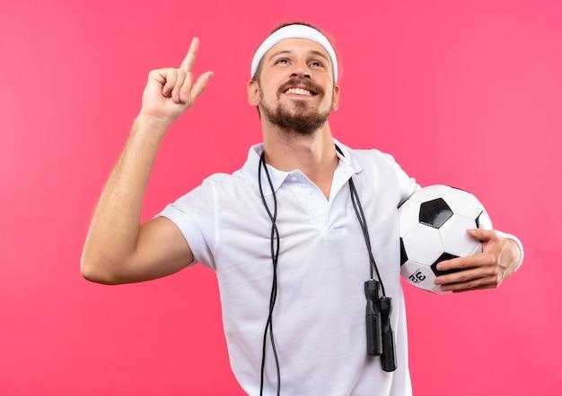 Lächelnder junger gutaussehender sportlicher mann, der stirnband und armbänder trägt, die fußball mit springseil um den hals lokalisiert auf rosa raum suchen und zeigen