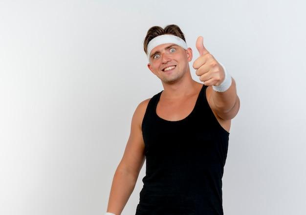 Lächelnder junger gutaussehender sportlicher mann, der stirnband und armbänder trägt, streckt hand aus und zeigt daumen oben vorne lokalisiert auf weißer wand