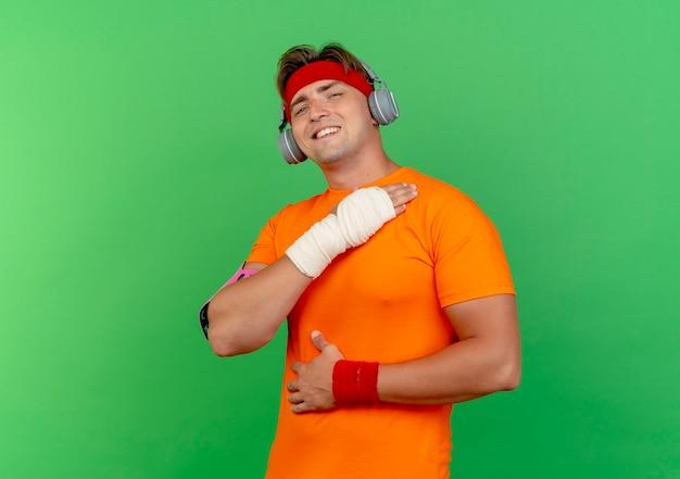 Lächelnder junger, gutaussehender, sportlicher mann mit stirnband und armbändern und kopfhörern und telefonarmband mit verletztem handgelenk, das mit verband umwickelt ist und die hände auf brust und bauch legt putting