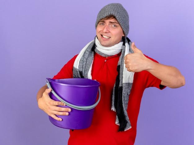 Lächelnder junger hübscher blonder kranker mann, der wintermütze und schal hält, der plastikeimer hält, der kamera zeigt daumen oben isoliert auf lila hintergrund