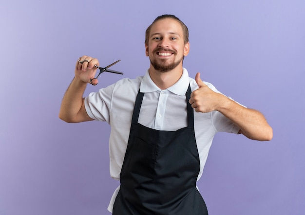 Lächelnder junger hübscher friseur, der uniform hält, die schere hält und daumen oben auf lila wand zeigt