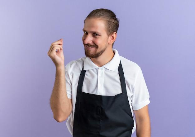 Lächelnder junger hübscher friseur, der uniform trägt, die geldgeste tut, lokalisiert auf lila wand