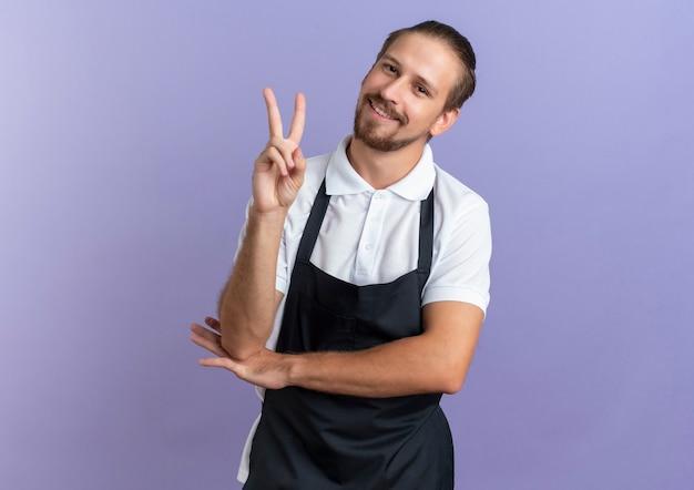 Lächelnder junger hübscher friseur, der uniform trägt, friedenszeichen tut und hand unter ellbogen lokalisiert auf lila wand setzt