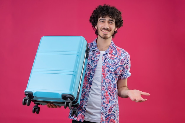 Lächelnder junger hübscher gelockter reisender mann, der koffer hält, der leere hand auf isolierter rosa wand zeigt