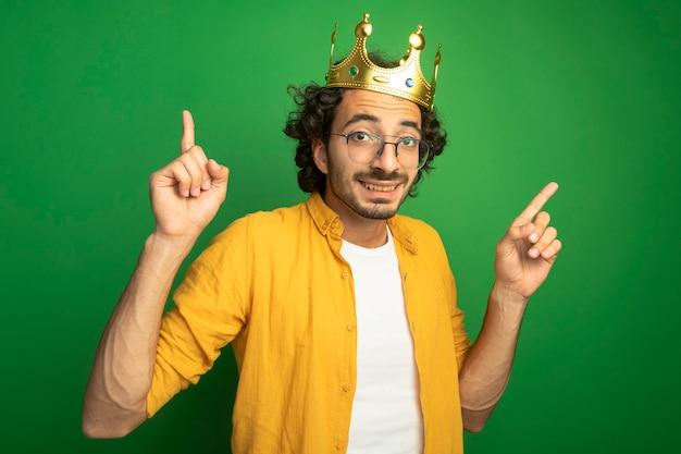 Lächelnder junger hübscher kaukasischer mann, der brille und krone trägt, die lokal auf grüner wand zeigen