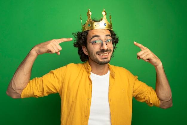 Lächelnder junger hübscher kaukasischer mann, der brille und krone trägt, zeigt auf seine krone, die kamera lokalisiert auf grünem hintergrund betrachtet