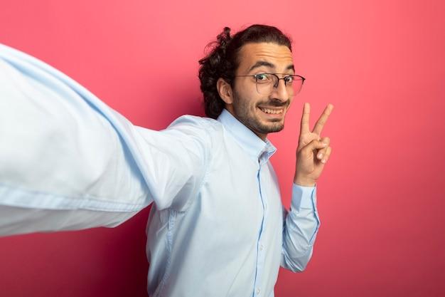 Lächelnder junger hübscher kaukasischer mann, der brillen trägt, die kamera betrachten, die hand in richtung kamera ausdehnt, die friedenszeichen lokalisiert auf purpurrotem hintergrund mit kopienraum tut
