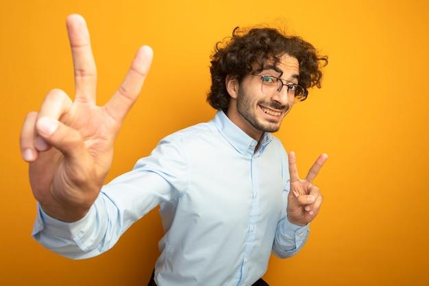 Lächelnder junger hübscher kaukasischer mann, der brillen trägt, die kamera betrachten, die hand in richtung kamera streckt, die friedenszeichen lokalisiert auf orange hintergrund mit kopienraum tut
