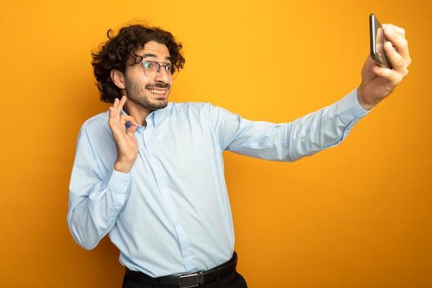 Lächelnder junger hübscher kaukasischer mann, der brillen trägt, die ok zeichen nehmen, das selfie lokalisiert auf orange hintergrund nimmt