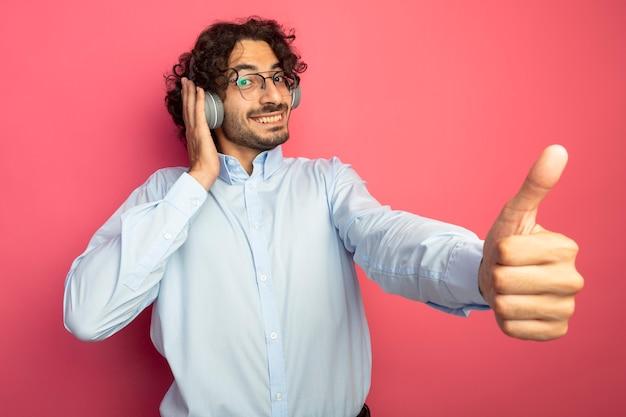 Lächelnder junger hübscher kaukasischer mann, der brillen und kopfhörer trägt, die kamera betrachten hand auf kopfhörer zeigen daumen oben isoliert auf purpurrotem hintergrund