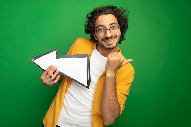 Lächelnder junger hübscher kaukasischer mann, der die brille hält, die pfeilmarkierung hält, die zur seite zeigt, die kamera zeigt, die zur seite zeigt, lokalisiert auf grünem hintergrund mit kopienraum