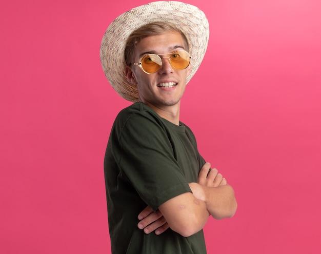 Lächelnder junger hübscher kerl, der grünes hemd und brille mit hutkreuzungshänden lokalisiert auf rosa wand mit kopienraum trägt