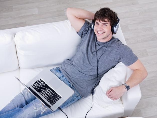 Lächelnder junger hübscher kerl, der musik im kopfhörer vom laptop hört - hoher winkel