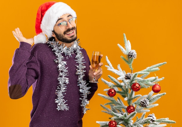 Lächelnder junger hübscher kerl, der nahe weihnachtsbaum steht, der weihnachtshut mit girlande auf hals hält, der glas champagner lokalisiert auf orange hintergrund hält