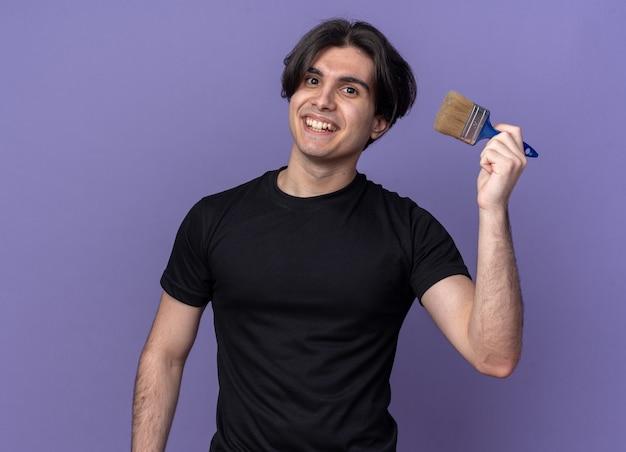 Lächelnder junger hübscher kerl, der schwarzen t-shirt hält, der pinsel lokalisiert auf lila wand hält