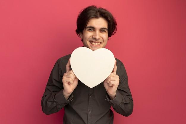 Lächelnder junger hübscher kerl, der schwarzes t-shirt hält, das herzformbox lokalisiert auf rosa wand hält