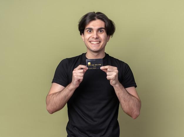 Lächelnder junger hübscher kerl, der schwarzes t-shirt hält, das kreditkarte lokalisiert auf olivgrüner wand hält