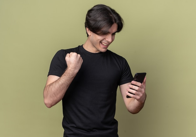 Lächelnder junger hübscher kerl, der schwarzes t-shirt hält telefon hält, das ja geste lokalisiert auf olivgrüner wand zeigt