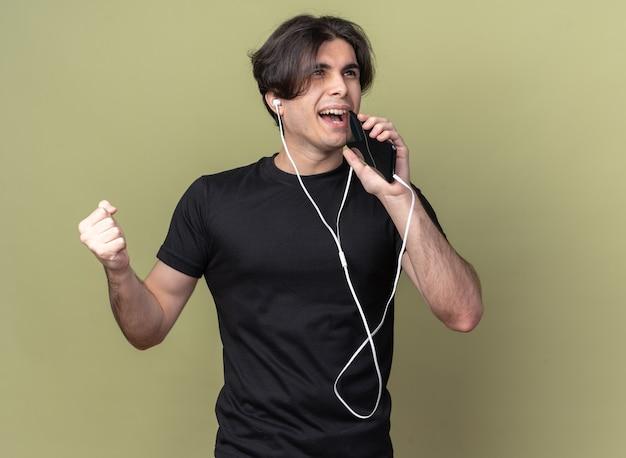 Lächelnder junger hübscher kerl, der schwarzes t-shirt mit kopfhörern hält telefon und singt isoliert auf olivgrüner wand trägt