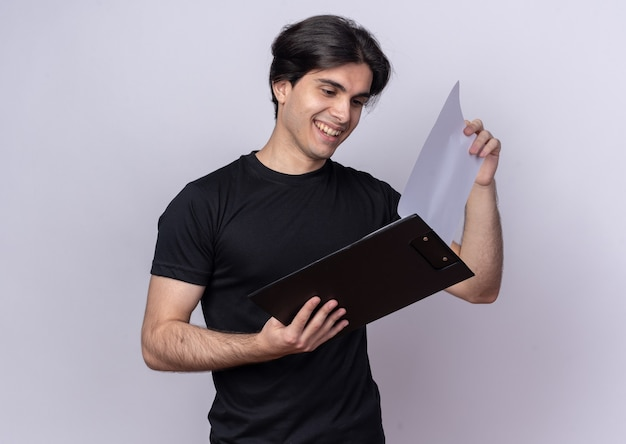 Lächelnder junger hübscher kerl, der schwarzes t-shirt trägt, das durch klemmbrett flippt, das auf weißer wand isoliert wird
