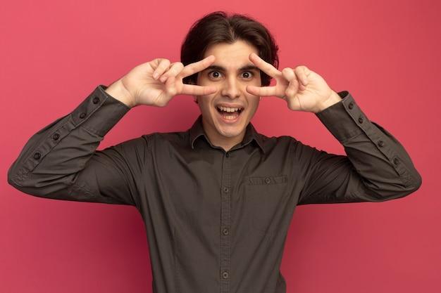Lächelnder junger hübscher kerl, der schwarzes t-shirt trägt, das friedensgeste lokalisiert auf rosa wand zeigt