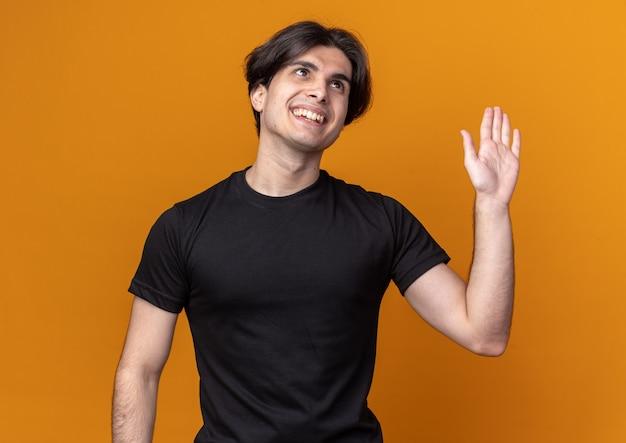 Lächelnder junger hübscher kerl, der schwarzes t-shirt trägt, das hallo geste lokalisiert auf orange wand zeigt