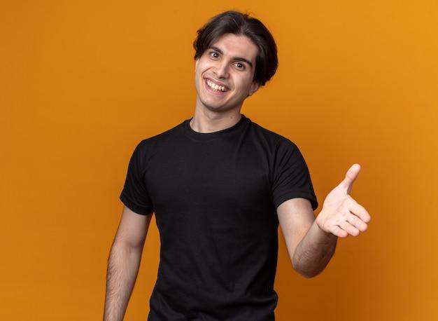 Lächelnder junger hübscher kerl, der schwarzes t-shirt trägt, das hand an der front lokalisiert auf orange wand hält