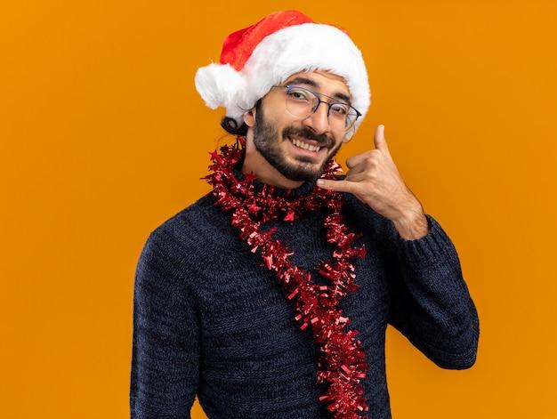 Lächelnder junger hübscher kerl, der weihnachtsmütze mit girlande am hals trägt telefonanrufgeste lokalisiert auf orange hintergrund trägt