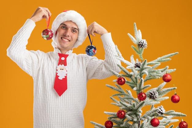 Lächelnder junger hübscher kerl, der weihnachtsmütze und weihnachtsmann-krawatte trägt, die nahe verziertem weihnachtsbaum steht, der weihnachtsballverzierungen nahe kopf betrachtet, die kamera lokalisiert auf orange hintergrund betrachtet