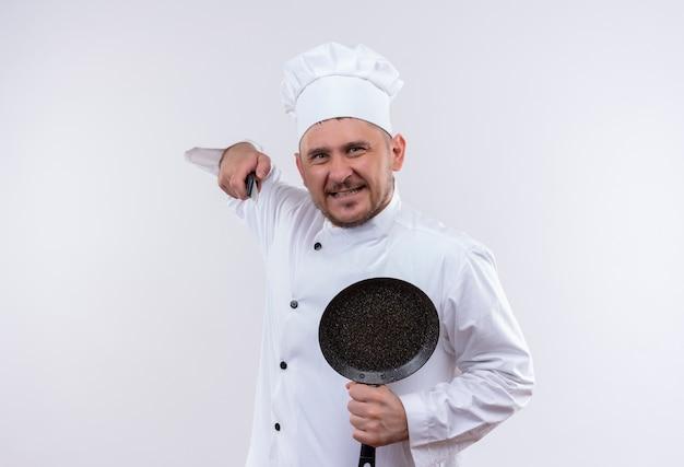 Lächelnder junger hübscher koch in der kochuniform, die bratpfanne hält und mit messer zeigt, das auf weißraum lokalisiert wird