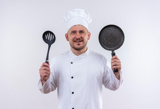 Lächelnder junger hübscher koch in der kochuniform, die geschlitzten löffel und bratpfanne auf lokalisiertem weißen raum hält