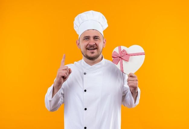 Lächelnder junger hübscher koch in der kochuniform, die herzförmige geschenkbox hält und finger auf lokalisiertem orange raum erhöht