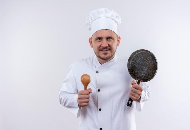Lächelnder junger hübscher koch in der kochuniform, die löffel und bratpfanne lokalisiert auf weißem raum hält