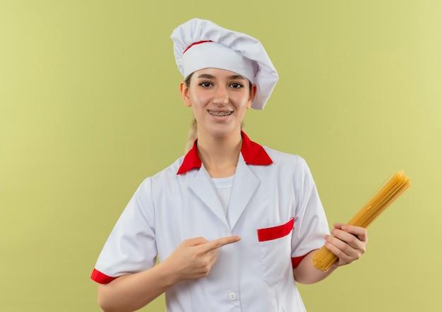 Lächelnder junger hübscher koch in der kochuniform mit zahnspangen, die auf spaghetti-nudeln halten und auf grünfläche lokalisiert zeigen